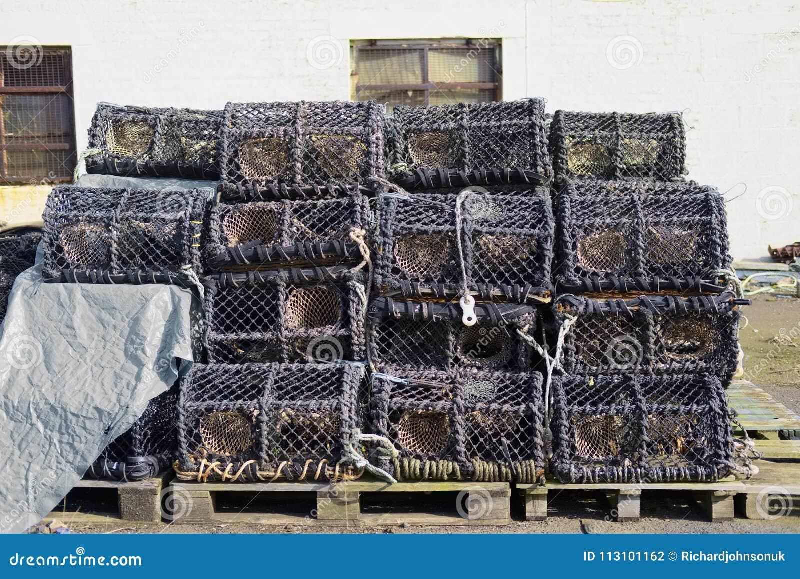 Os potenciômetros das cestas das redes dos cestos da lagosta empilham a pilha em cestas da rede de pesca dos fishermans do porto