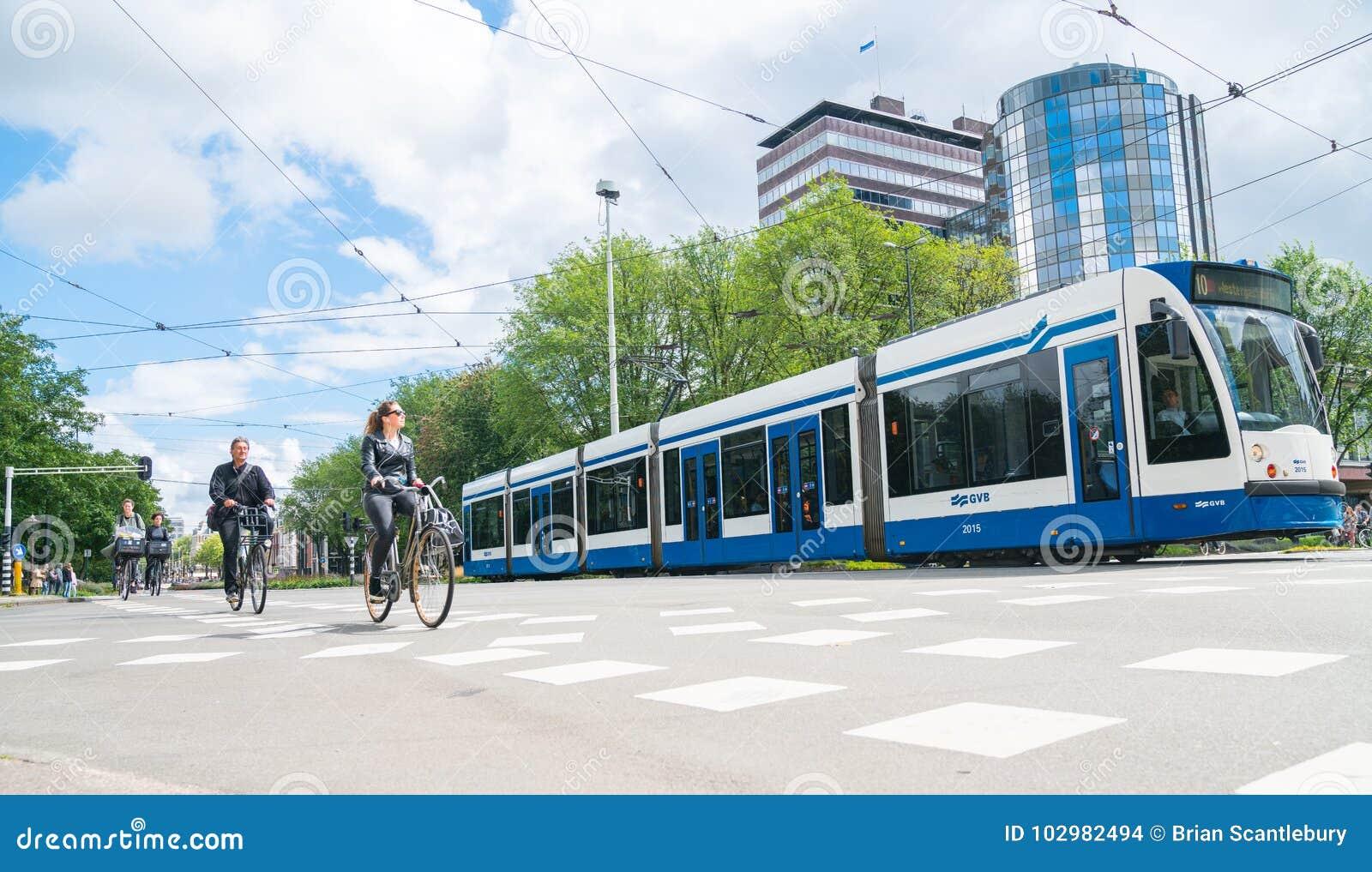 Os povos dão um ciclo com o bonde através da interseção da cidade com prédios de escritórios modernos no fundo