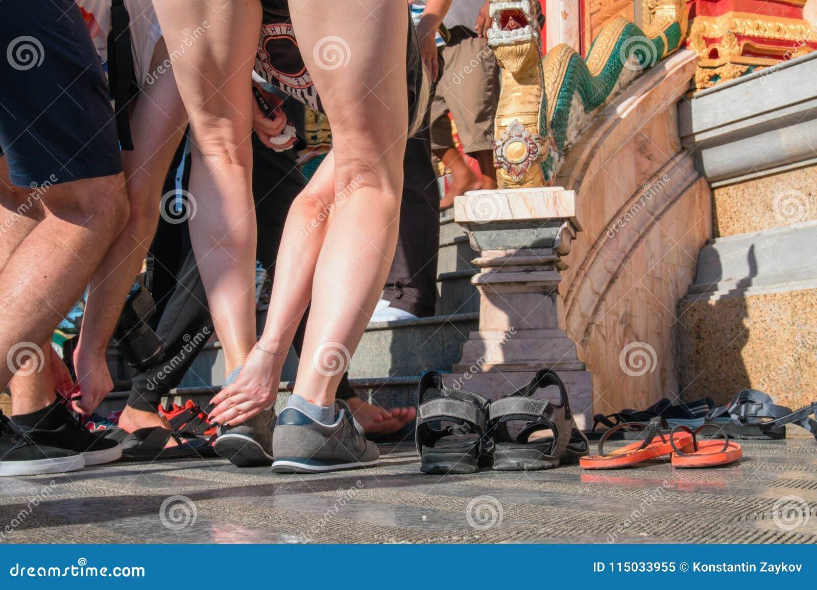 Os povos decolam suas sapatas antes de entrar no templo budista Conceito de observar tradições Conformidade com as regras