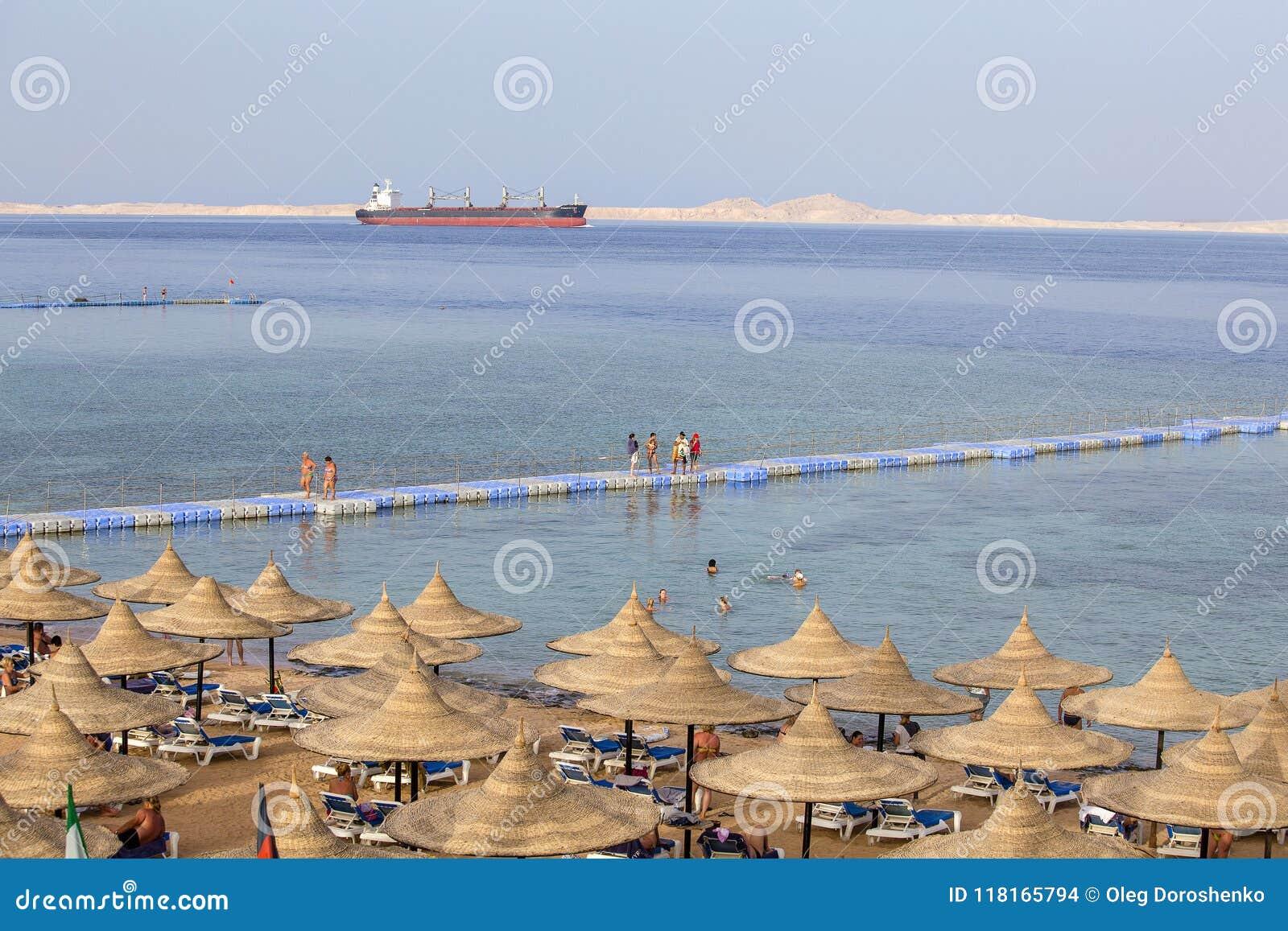 Os povos descansam na praia perto do Mar Vermelho na estância, Sharm el Sheikh, Egito