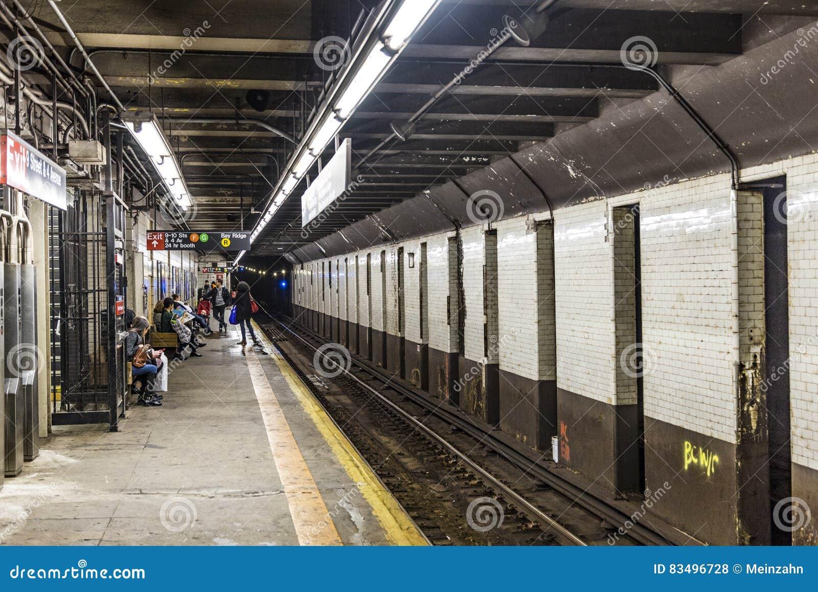 Os povos esperam rua da estação de metro na 9a em New York
