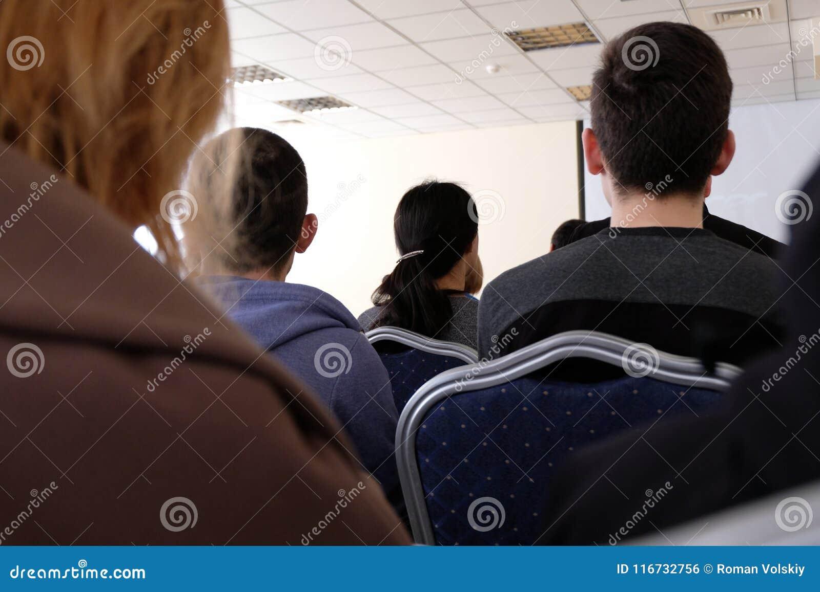 Os povos estão sentando-se no salão e estão escutando-se uma leitura Conceito do negócio