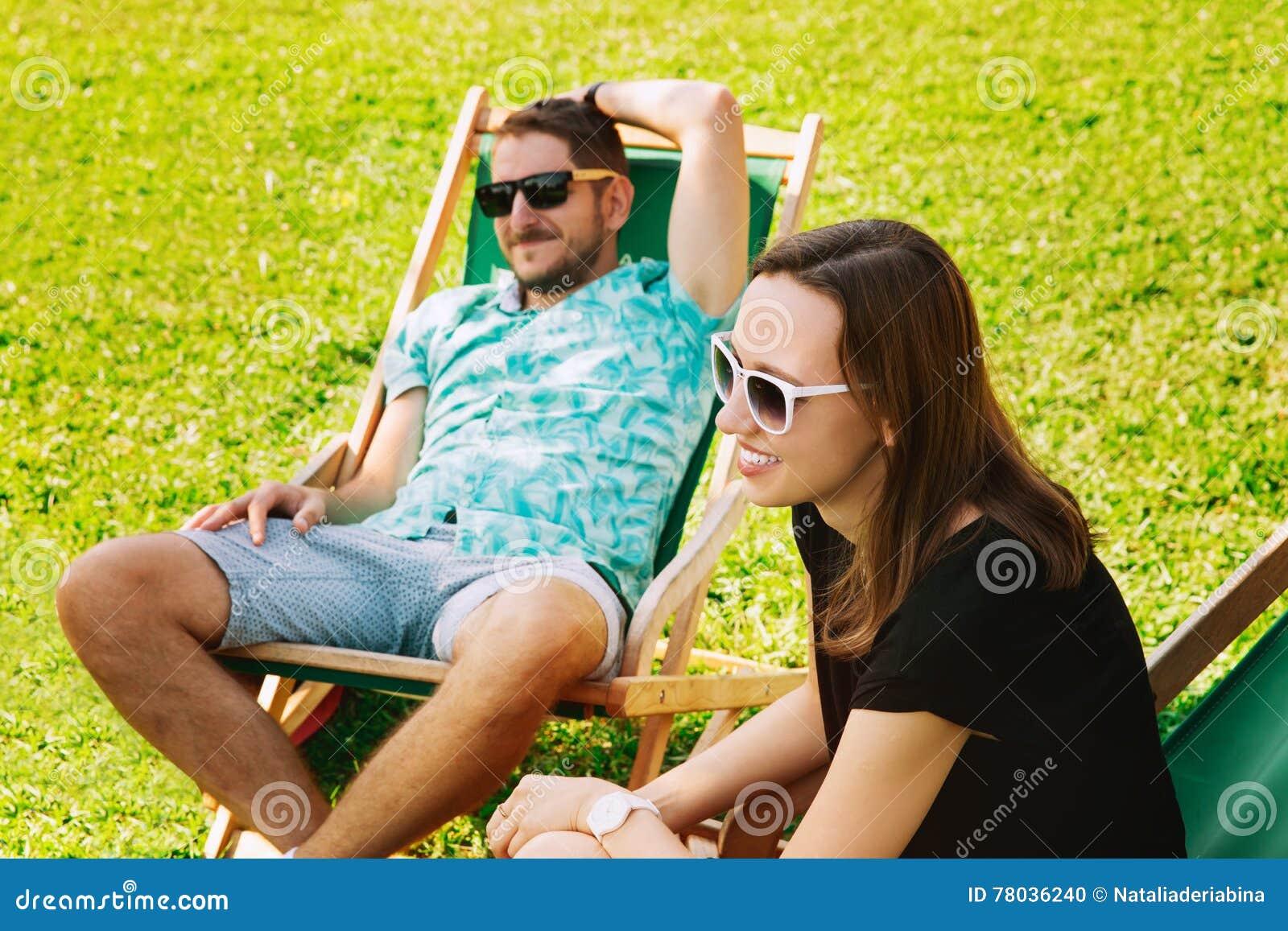 Os povos felizes que relaxam e comunicam exterior no relaxamento feliz da jovem mulher do fundo exterior