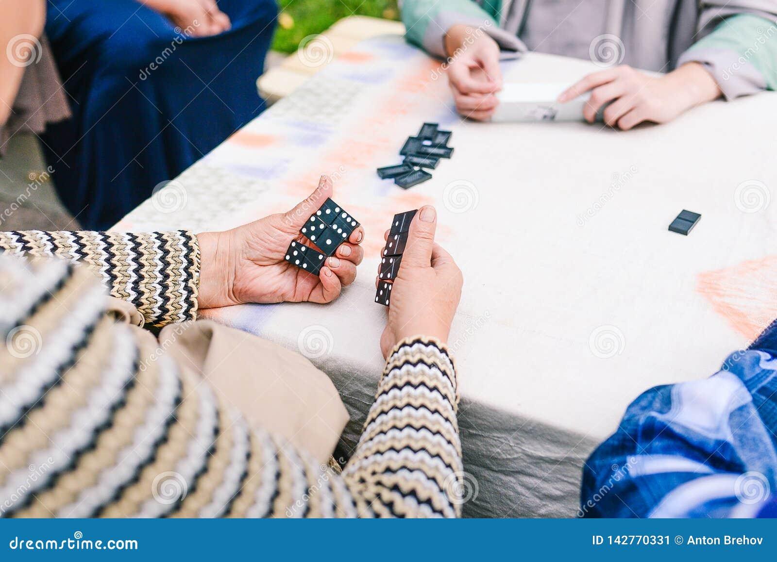 Os povos jogam dominós Diversos povos têm o divertimento que joga dominós na rua Jogo de mesa
