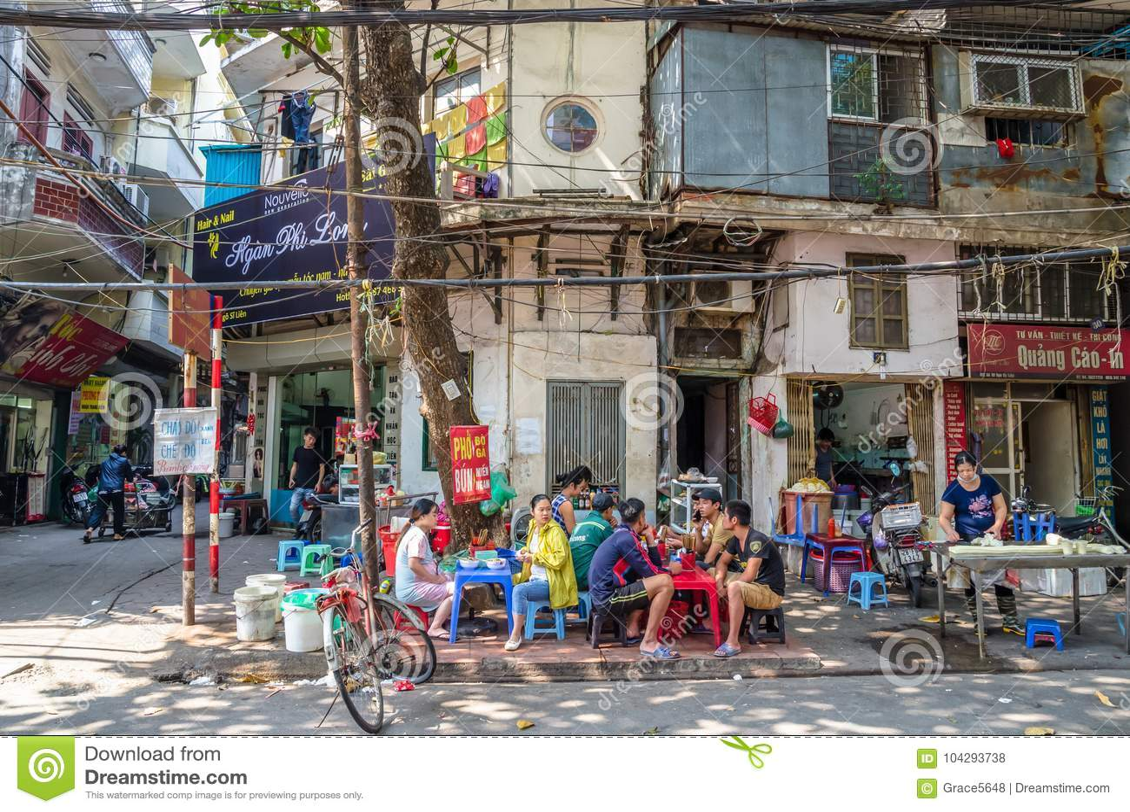 Os povos podem visto comendo seu alimento ao lado da rua na manhã em Hanoi, Vietname