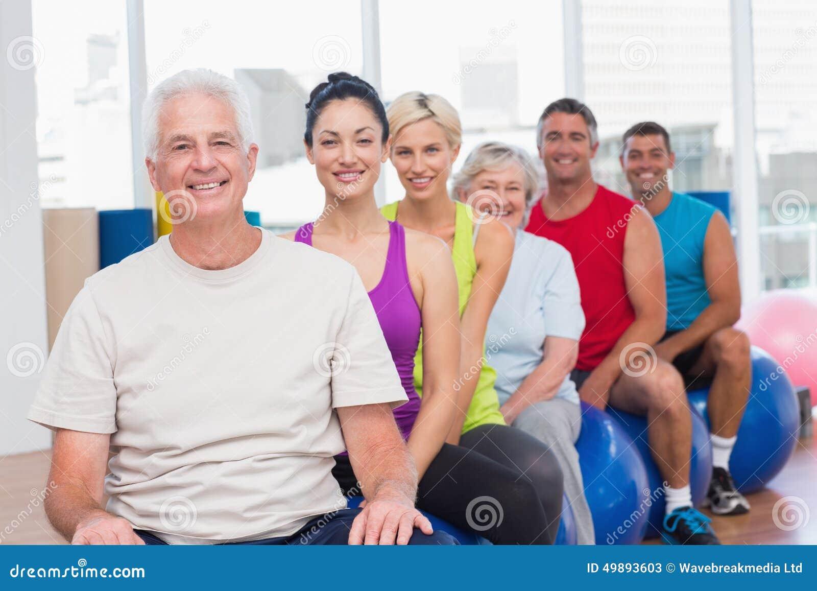 Os povos que relaxam em bolas da aptidão no gym classificam