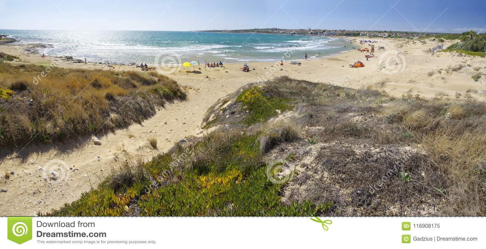 Os povos tomam o banho do sol na praia situada perto da cidade de Sampieri, Sicília