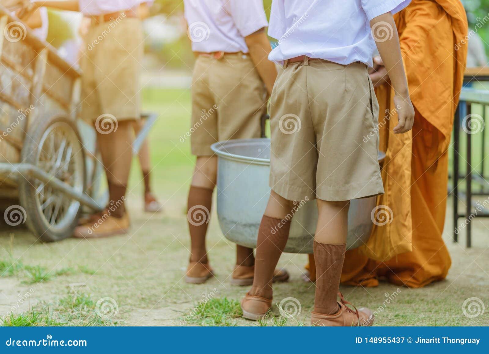Os professores e os estudantes fazem junto o m?rito para dar ofertas do alimento a uma monge budista em dias religiosos important
