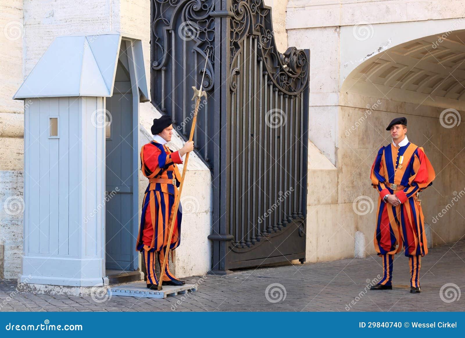 Os protetores suíços aproximam a basílica de St Peters em Roma, Italia