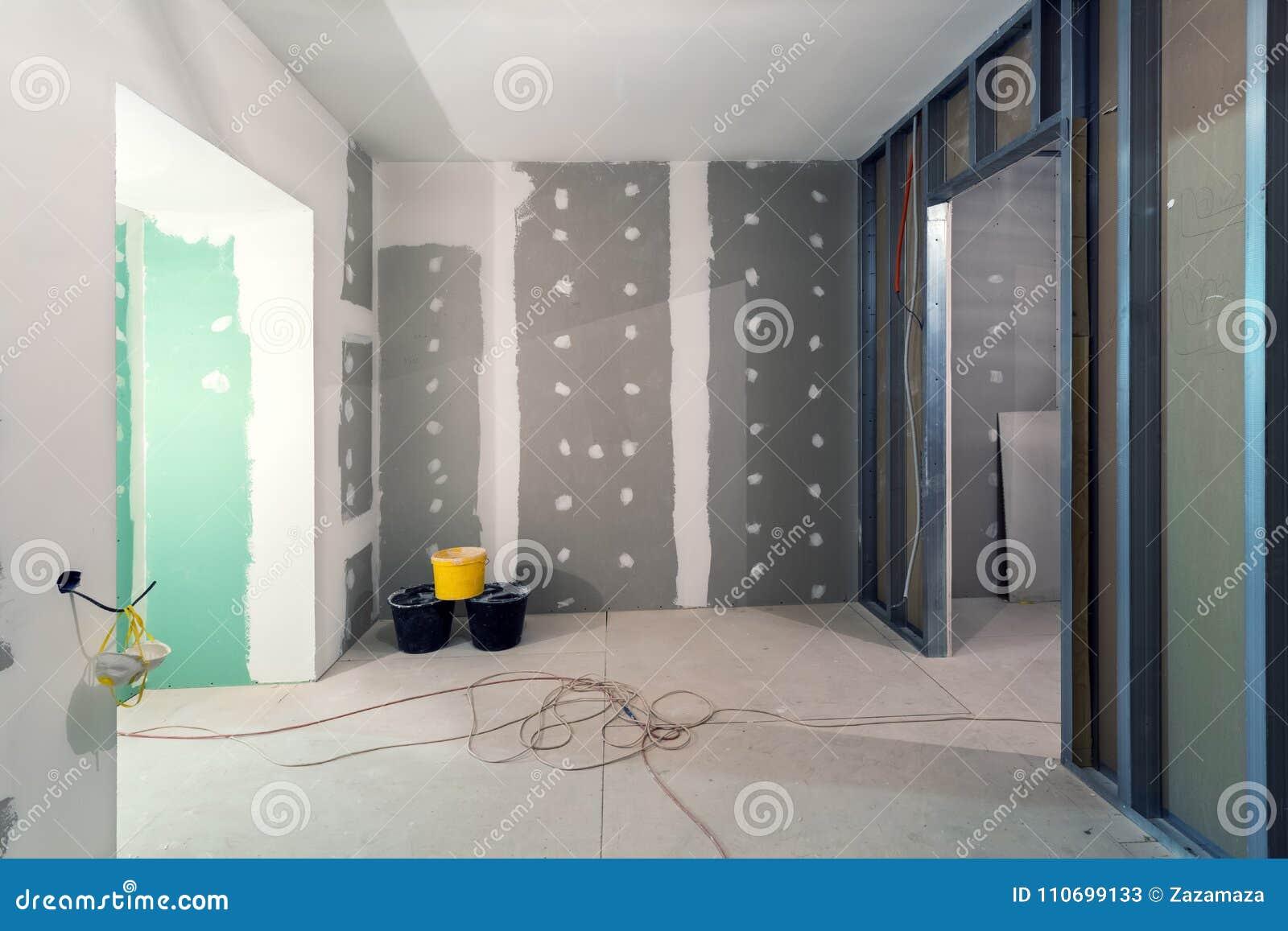 Os quadros do metal e o drywall da placa de gesso para paredes da gipsita, três cubetas e fios bondes no apartamento estão sob a