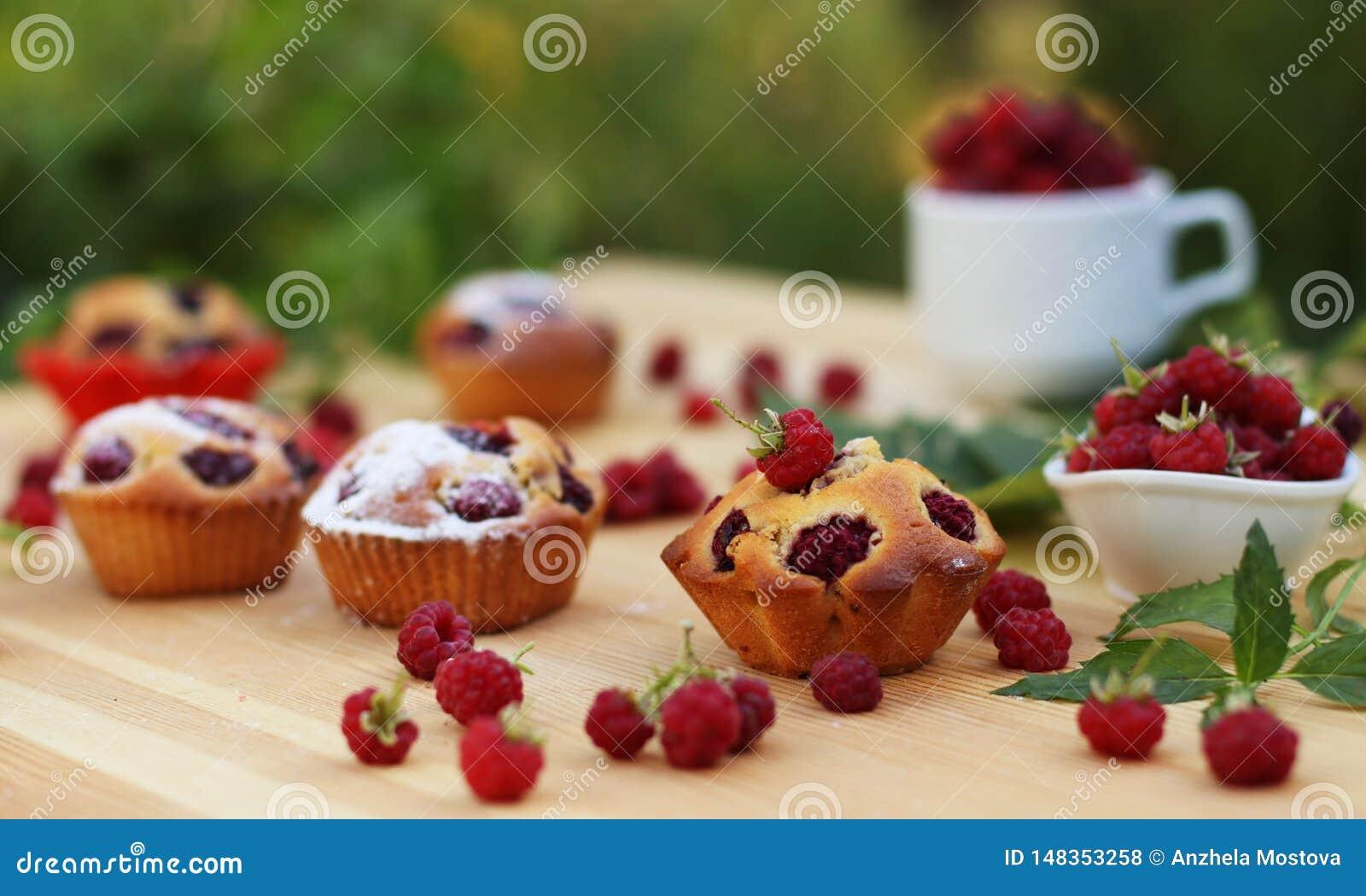Os queques com framboesas s?o ficados situados em uma tabela de madeira no fundo de arbustos verdes
