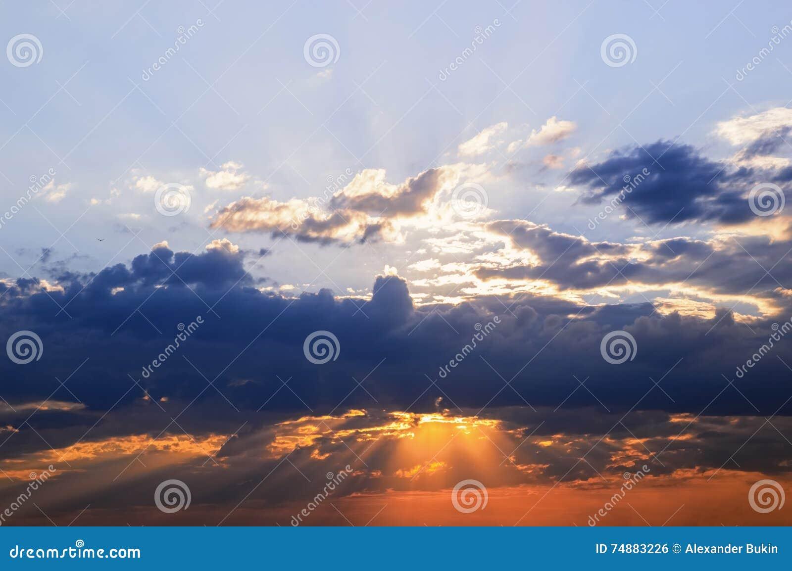 Os raios do sol fazem sua maneira através das nuvens, o céu