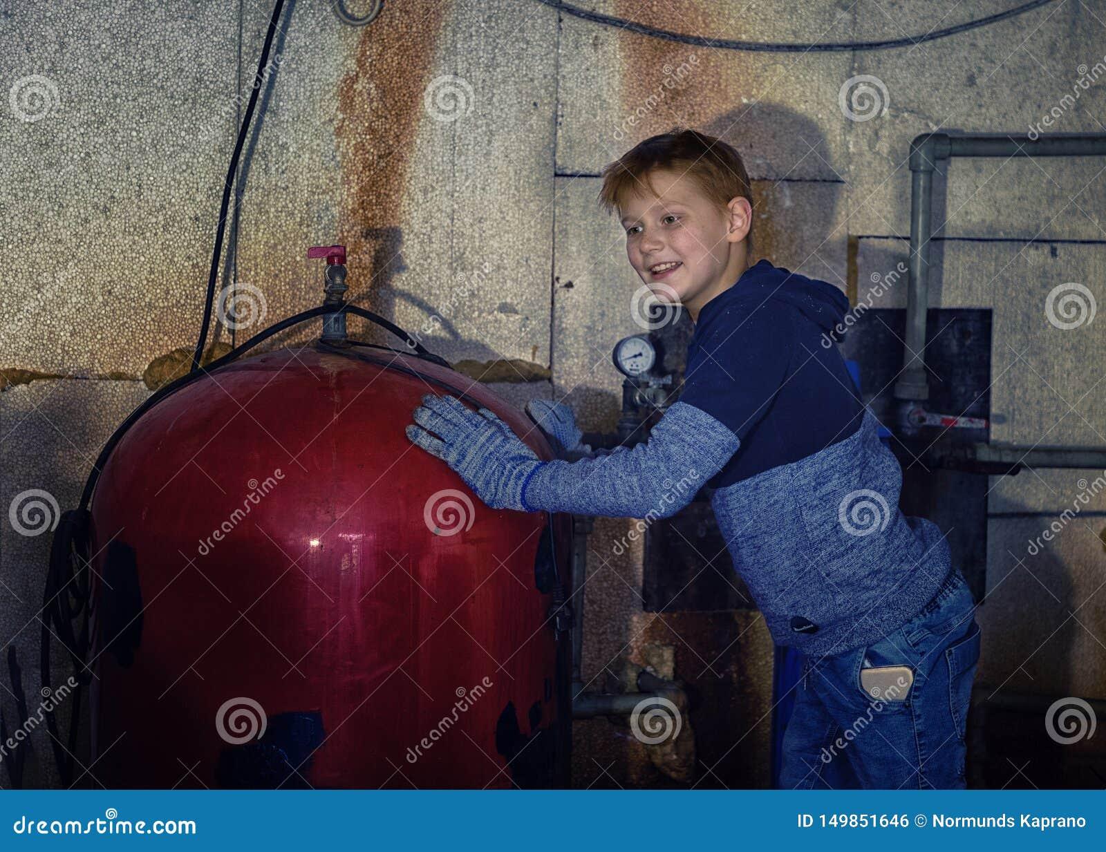Os reparos do rapaz pequeno molham caldeiras no porão