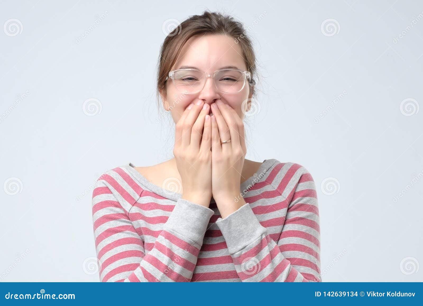 Os risos fêmeas novos alegremente, cobrem a boca enquanto as tentativas param de rir
