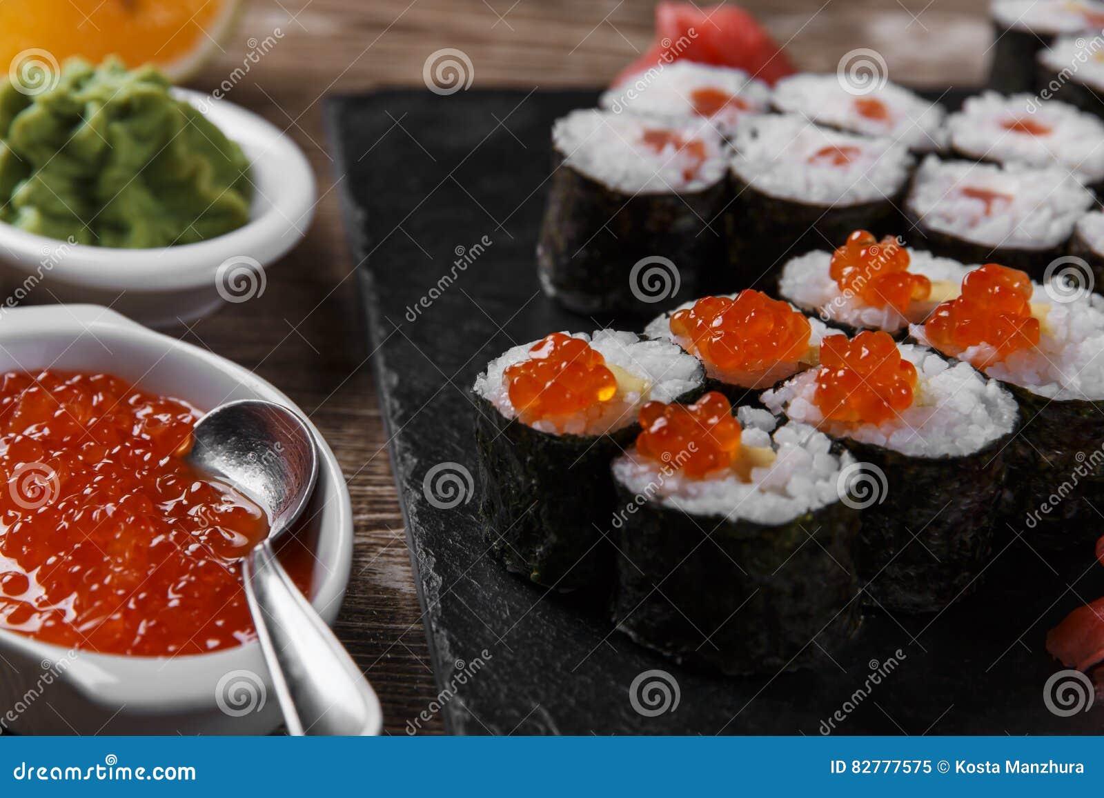 Os rolos e os ingredientes de sushi serviram em uma superfície de madeira