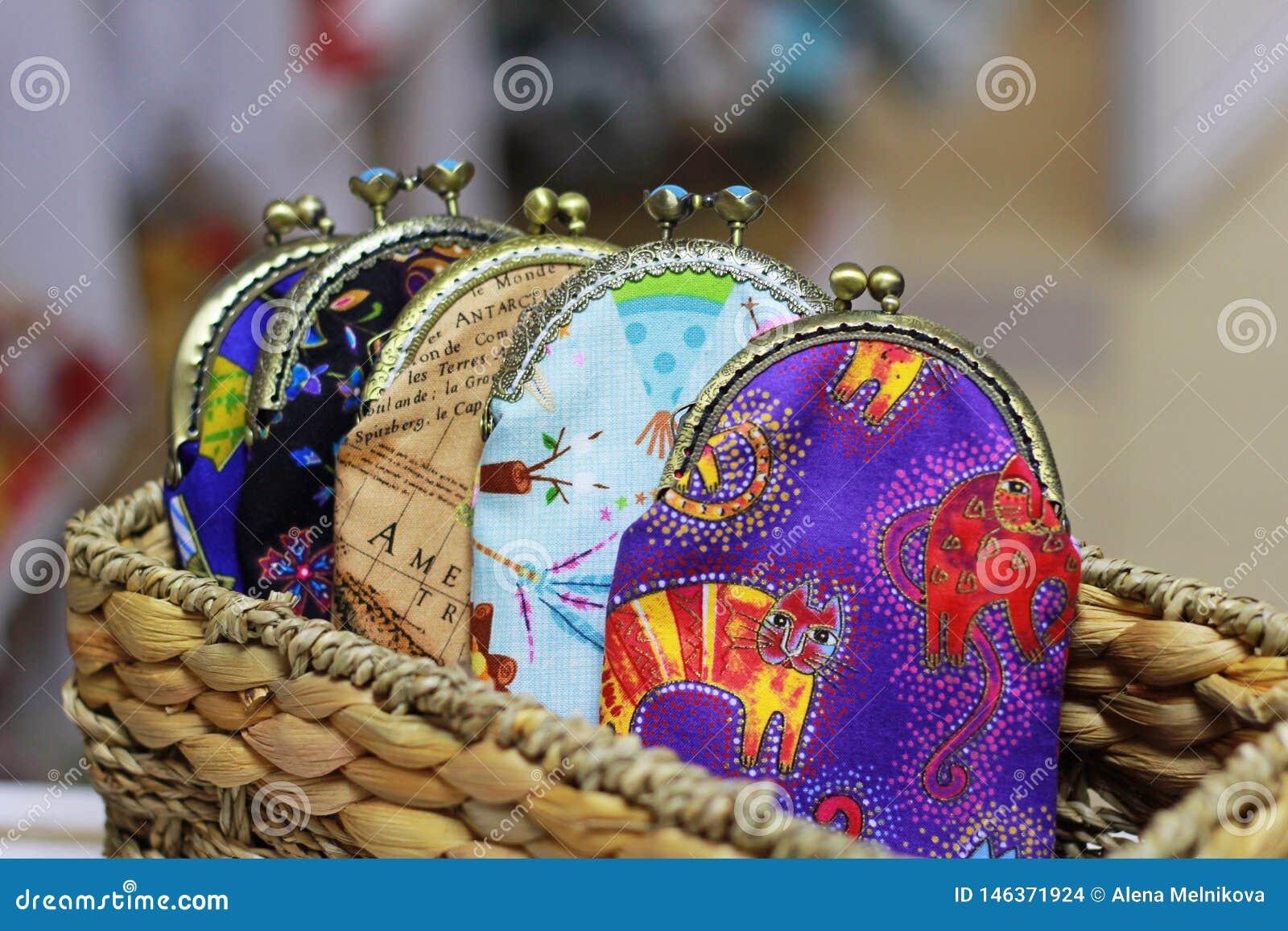 Os sacos coloridos para o dinheiro com um fecho do metal estão em uma cesta de vime