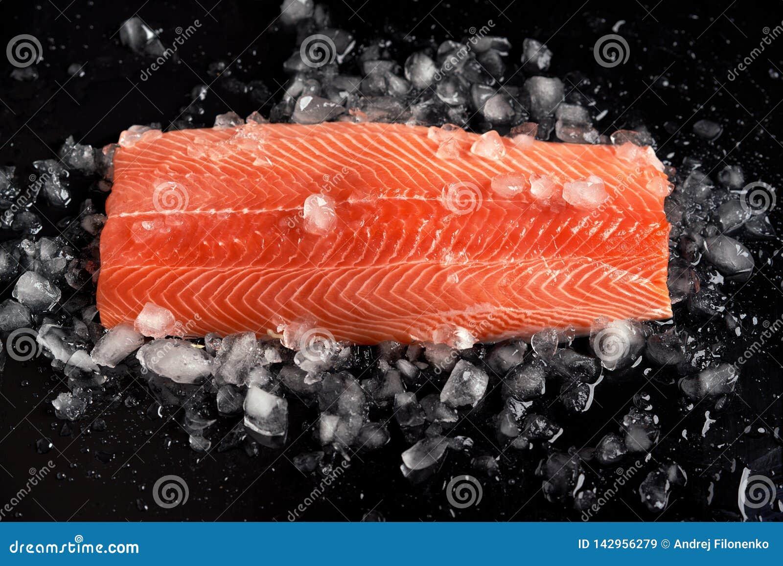 Os salmões crus enfaixam o todo no gelo lascado sobre o fundo preto Nutrição dietética Peixes vermelhos