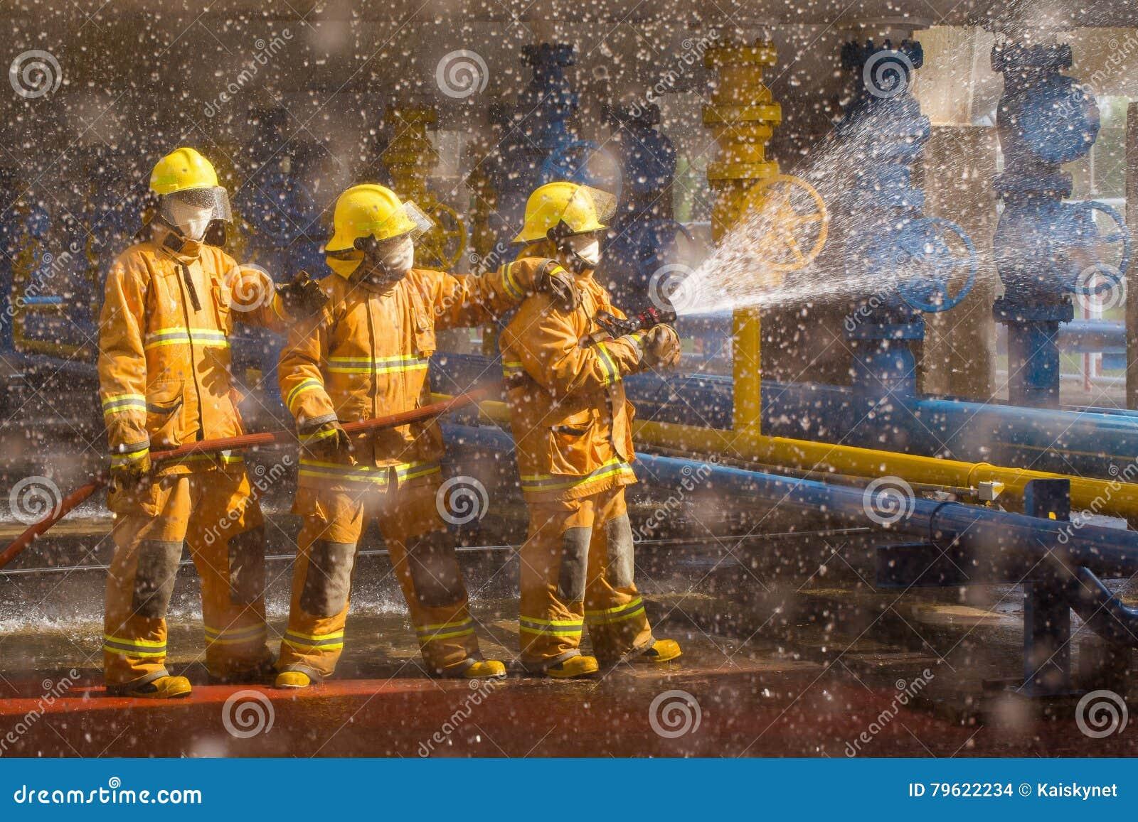 Os sapadores-bombeiros que treinam, primeiro plano são gota da gota Spr da água