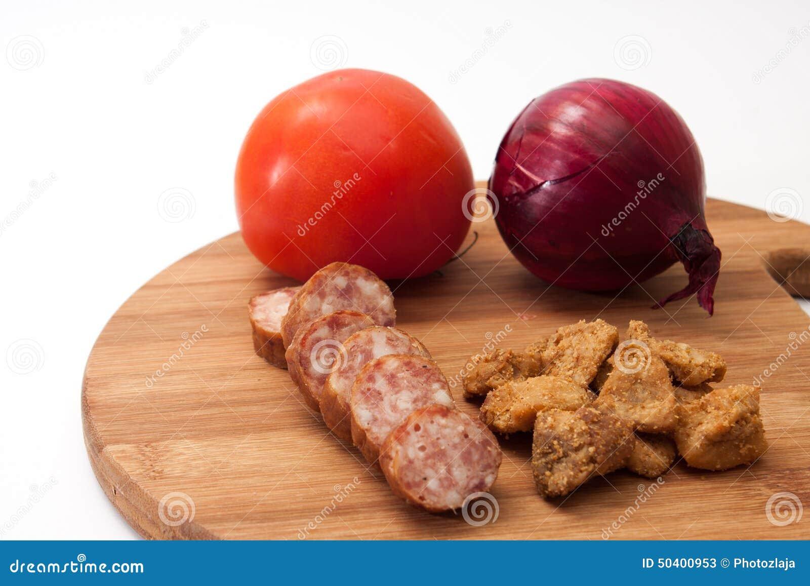 Os scratchings caseiros da salsicha e da carne de porco serviram com tomates e o