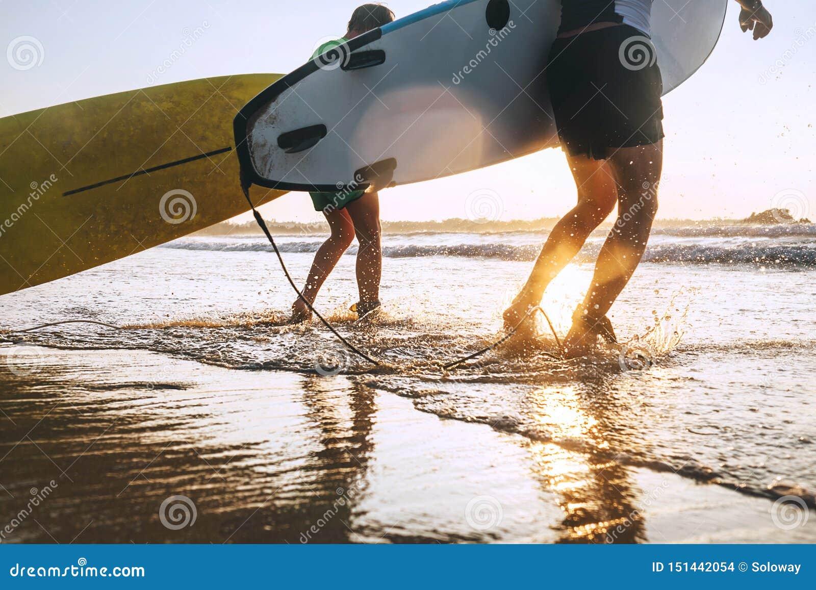 Os surfistas do filho e do pai correm em ondas de oceano com placas surfando