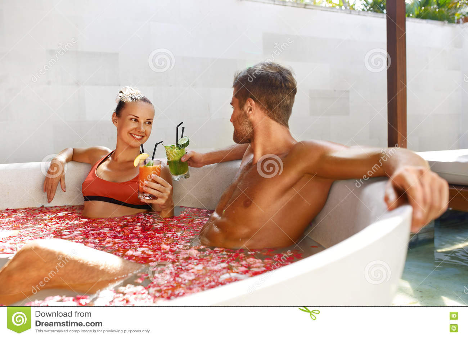 Os termas relaxam Pares no amor em bebidas bebendo do banho da flor