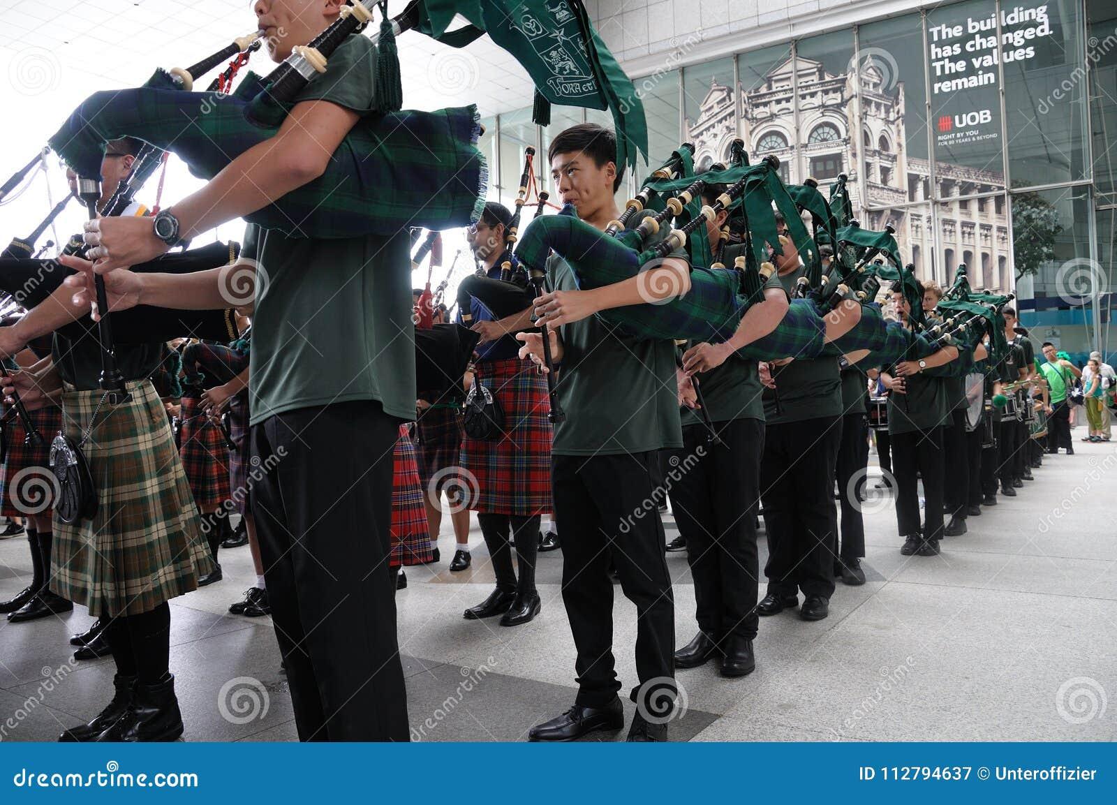 Os tocadores de gaita de foles unem recolhimentos na plaza de UOB em Singapura durante o dia 2018 do ` s de St Patrick