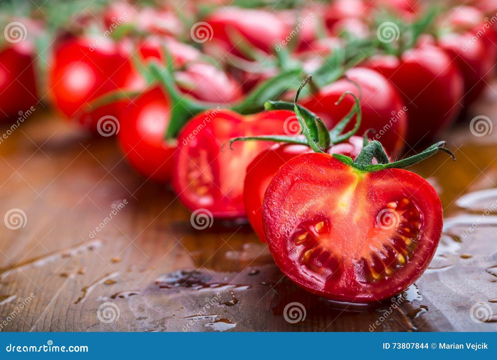 Os tomates de cereja frescos lavaram a agua potável Corte tomates frescos