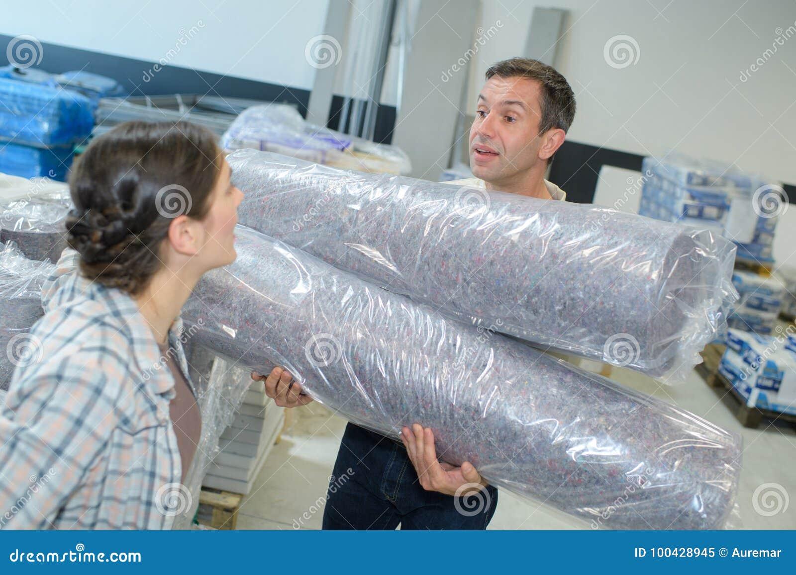 Os trabalhadores armazenam o transporte do empacotamento plástico