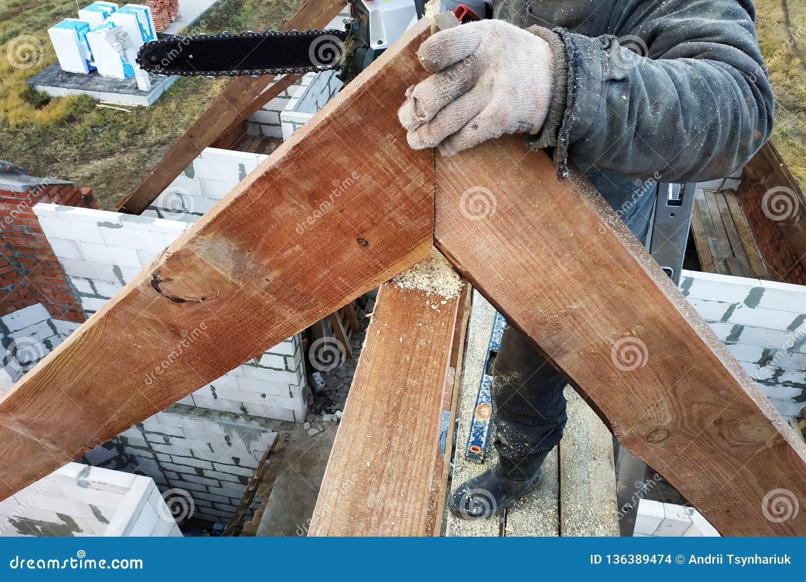 Os trabalhadores cortaram as vigas no telhado da casa da serra de cadeia