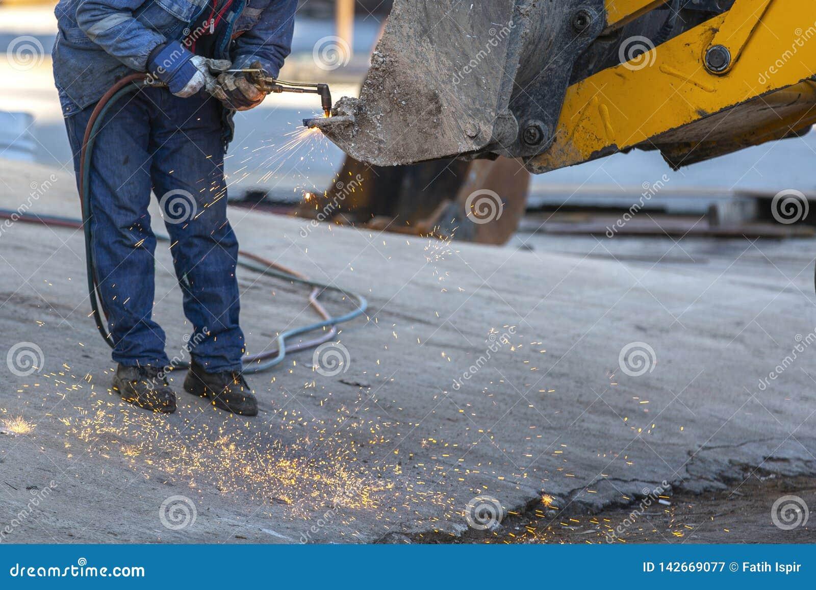Os trabalhadores que trabalham máquinas de soldadura do dia
