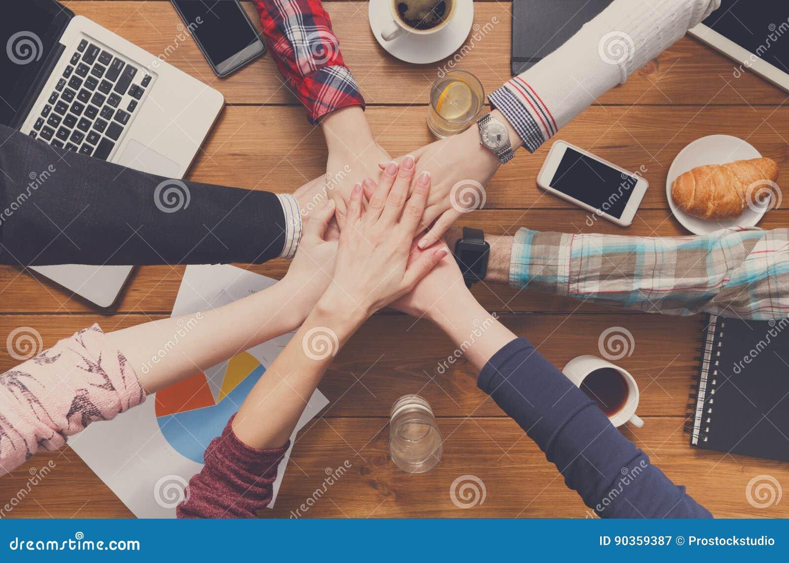 Os trabalhos de equipa e o conceito teambuilding no escritório, pessoa conectam as mãos