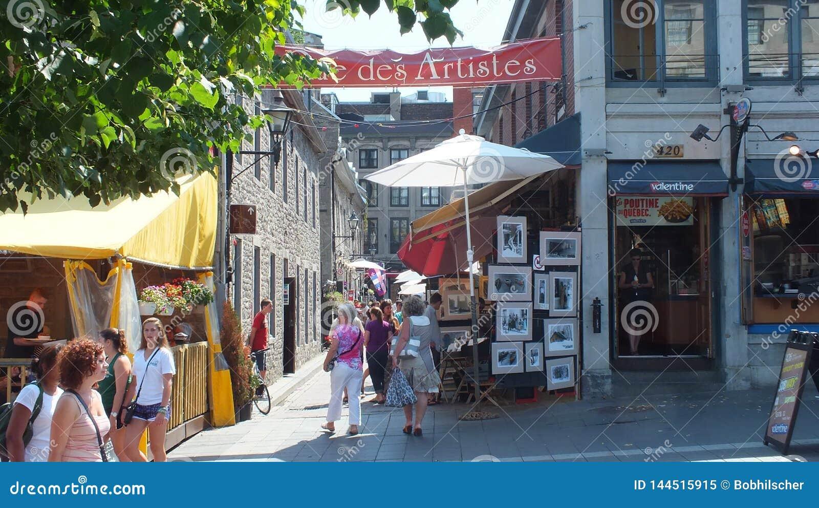 Os turistas apreciam o distrito dos artists do DES da rua em Montreal