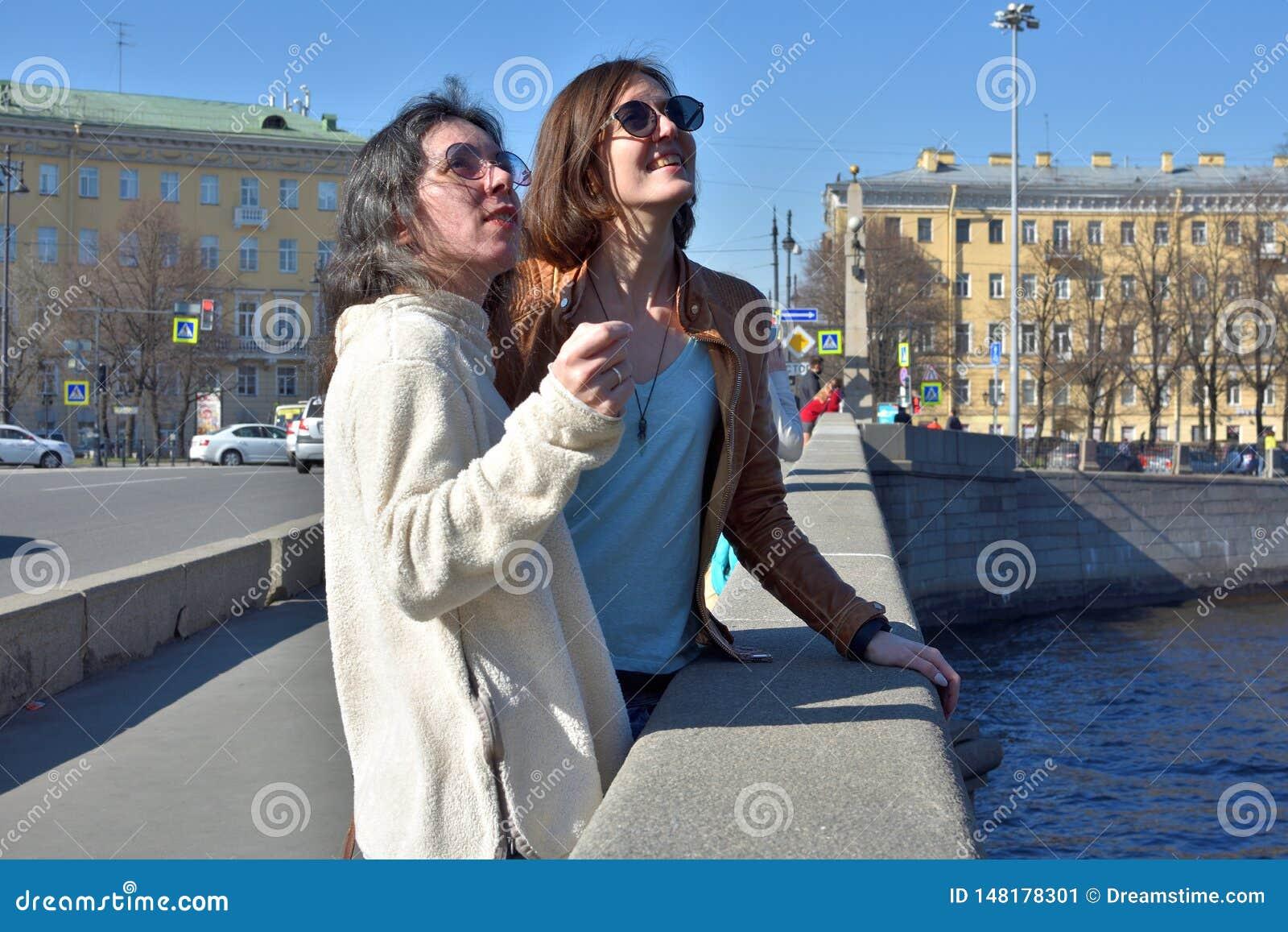 Os turistas das jovens senhoras no suporte de St Petersburg R?ssia em uma ponte no constru??es amarelas esquadram e olham detalhe