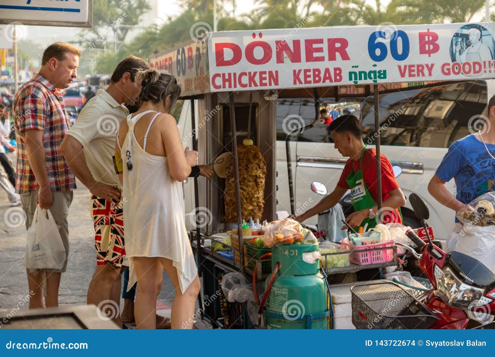 Os turistas estão em uma tenda móvel e compram no espeto