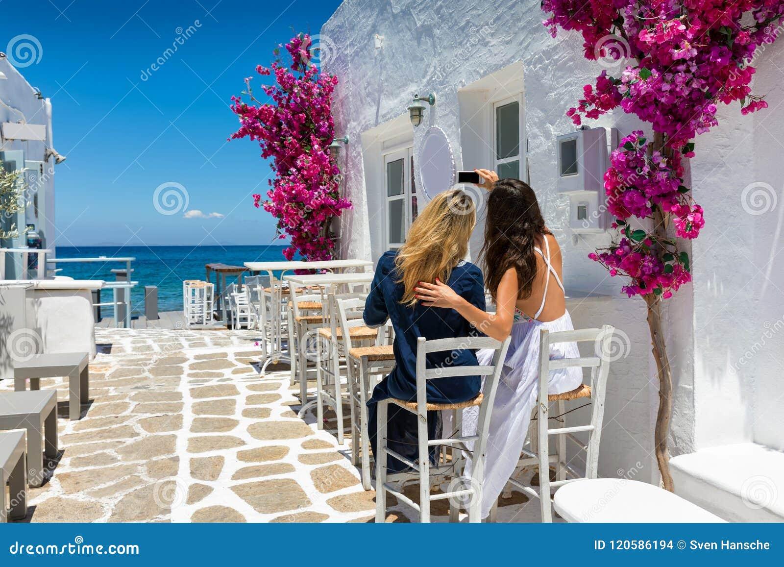 Os turistas fêmeas estão tomando uma foto do selfie nas aleias whitewashed da vila de Naousa em Paros