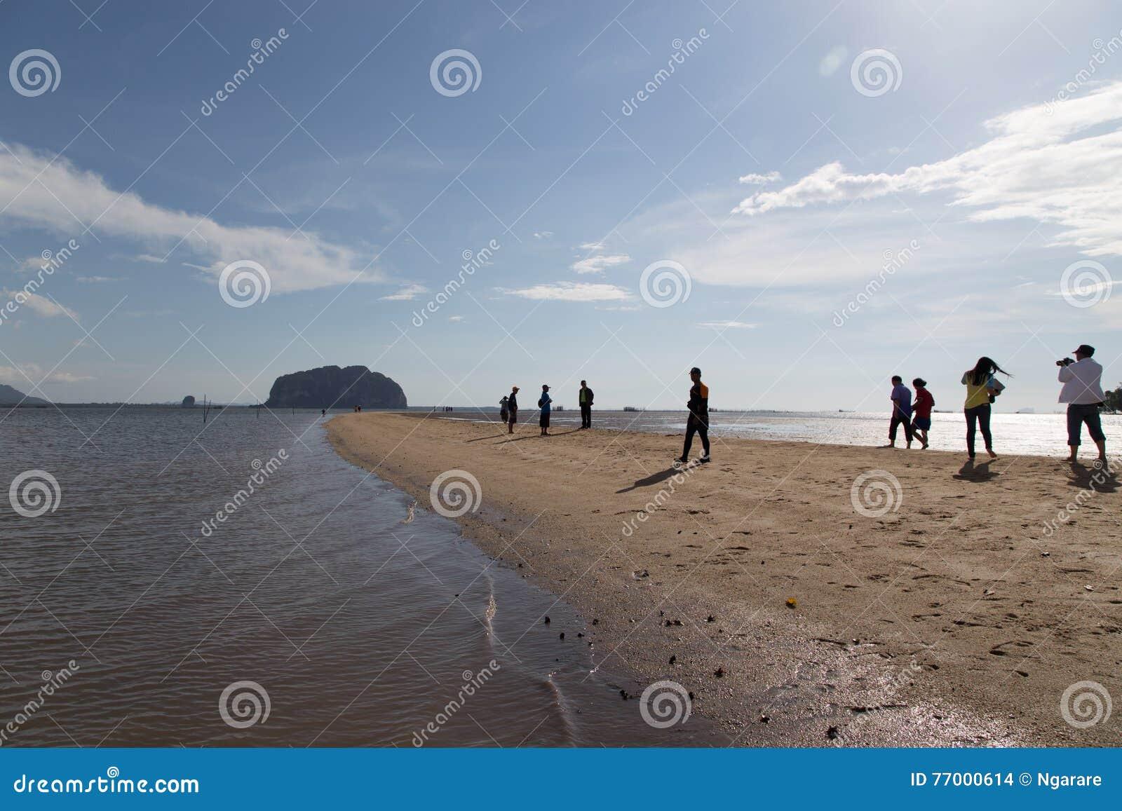 Os turistas visitam a escala dourada Dragon Spine Beach