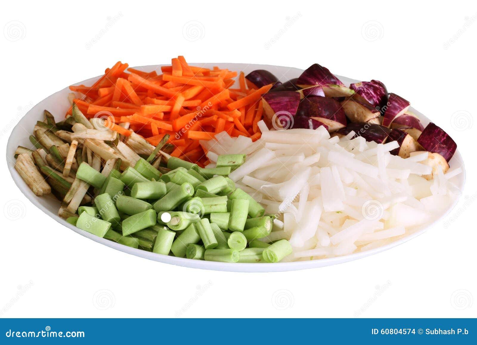 Os vegetais coloridos arranjaram na placa com fundo branco