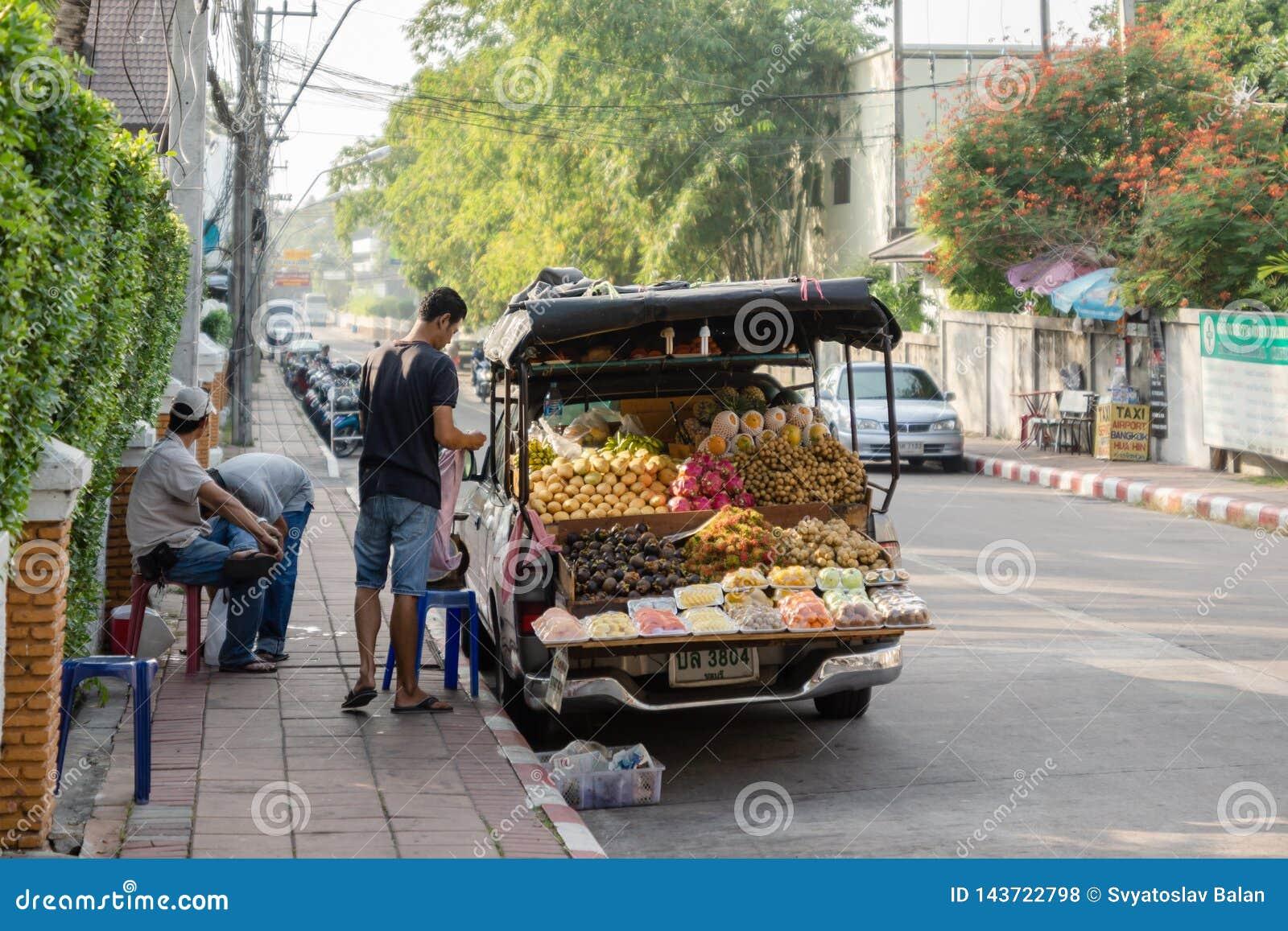 Os vendedores do fruto fresco estão preparando-se para trocar cedo na manhã em uma rua em Pattaya