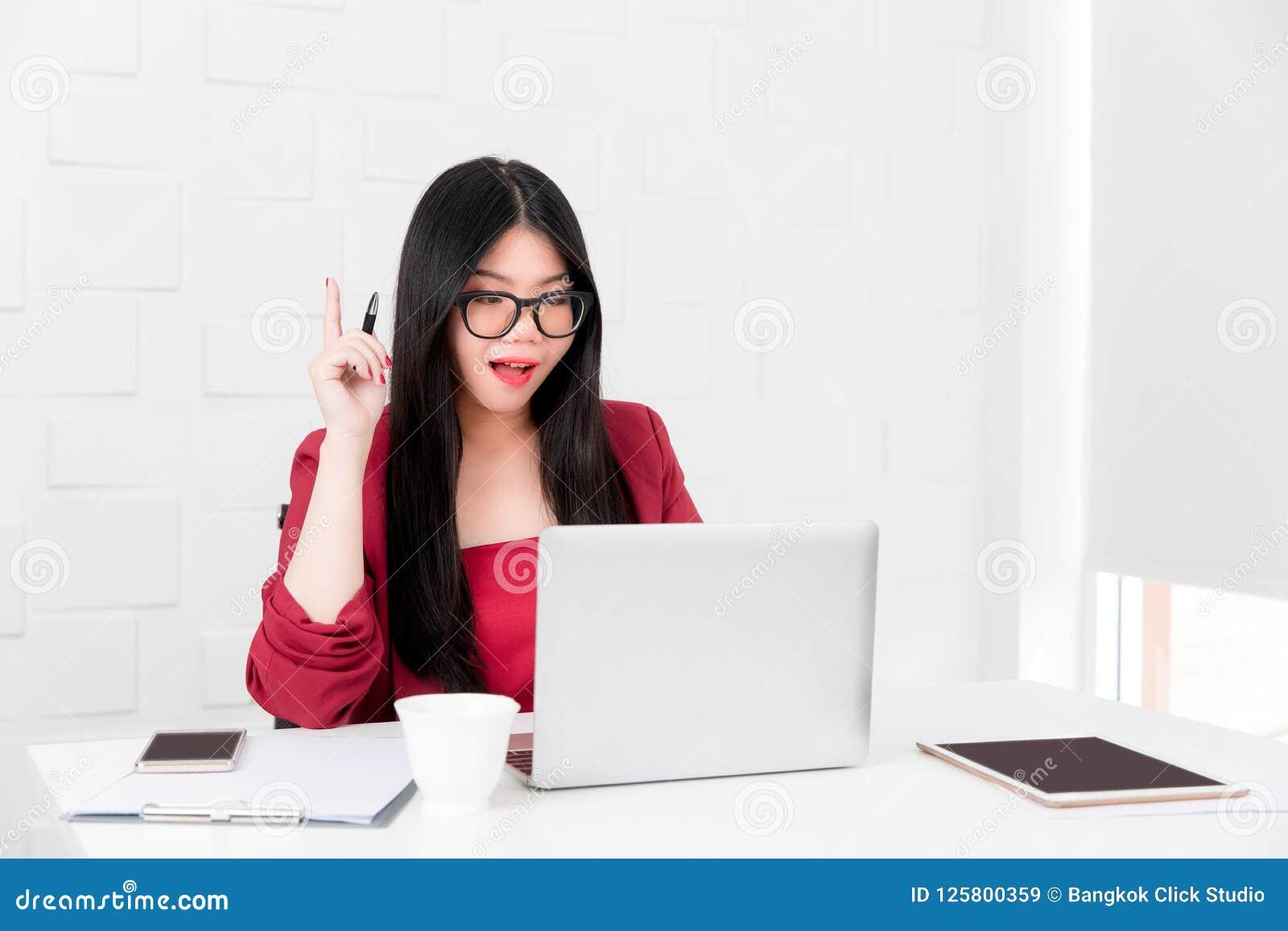 Os vidros asiáticos de Wearing da mulher de negócios e um terno vermelho estão sentando a
