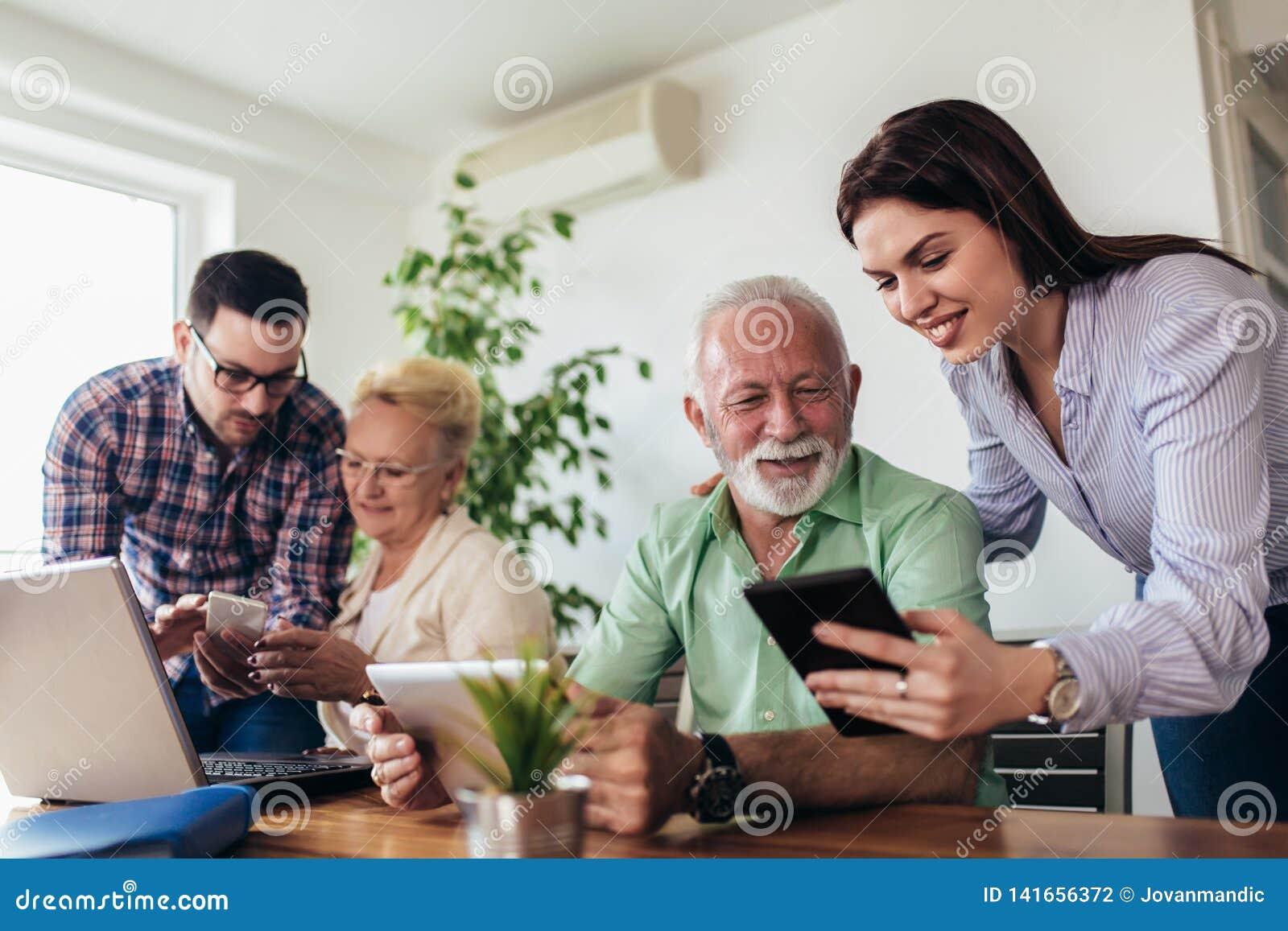 Os voluntários ajudam povos superiores no computador Jovens que dão a introdução superior dos povos ao Internet