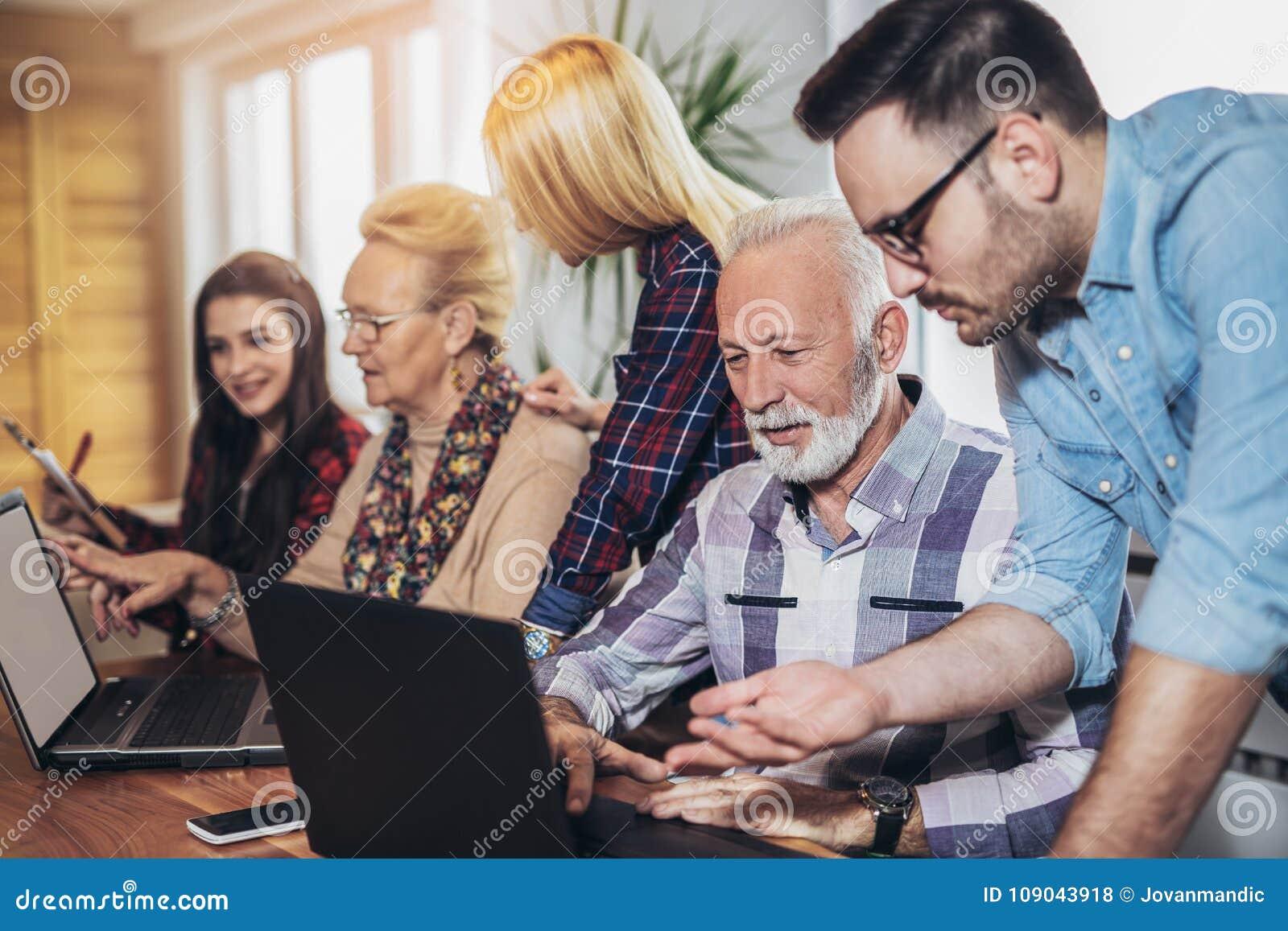 Os voluntários novos ajudam povos superiores no computador