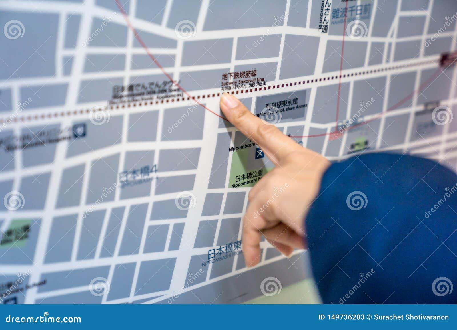 Osaka, Japón - 3 de marzo de 2018: El viajero lee y señalar al mapa del tren del metro del subterráneo del Japón en el tablero ,