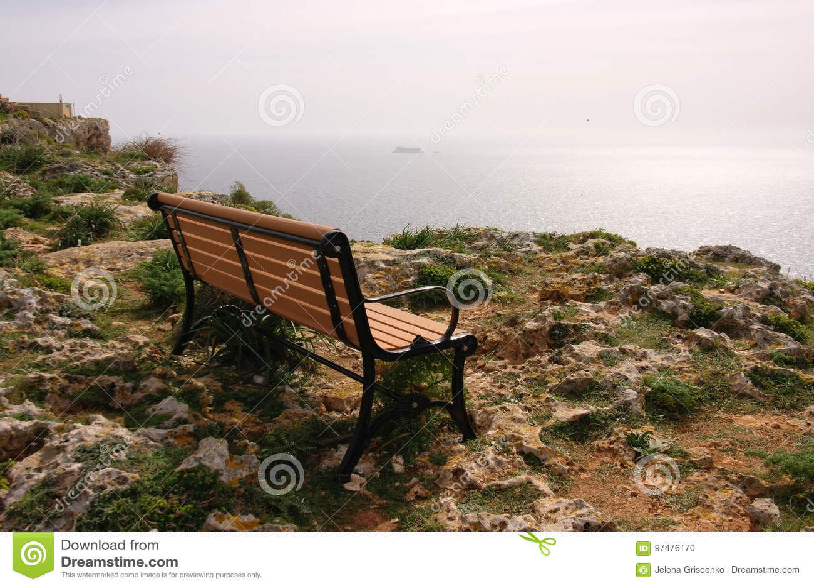 Osamotniona ławka na skalistym oceanu wybrzeżu