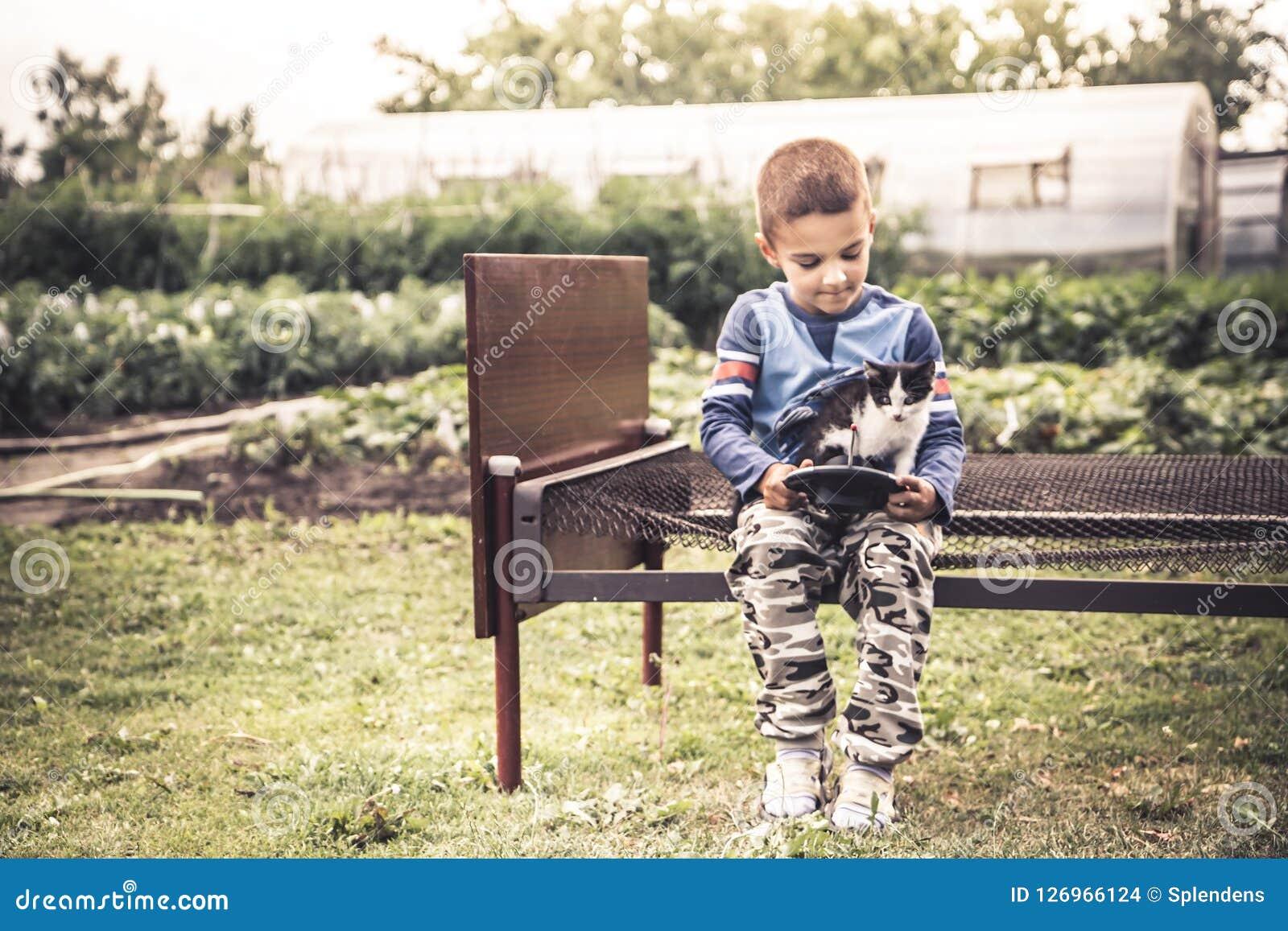 Osamotniona dziecko dzieciaka chłopiec bawić się figlarki wsi stylu życia pojęcia samotność i zwierzę domowe opieki przyjaźń