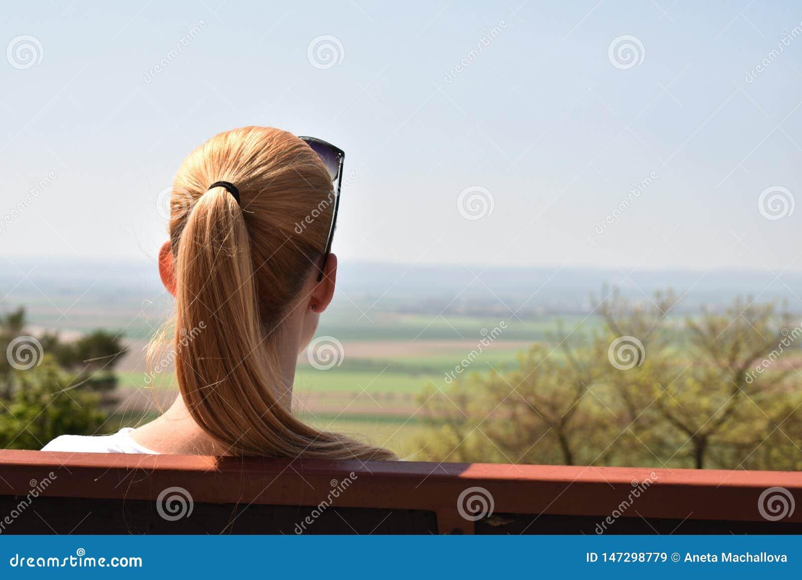 Osamotnionej kobiety tylni widok patrzeje odpowiadać obsiadanie na ławce