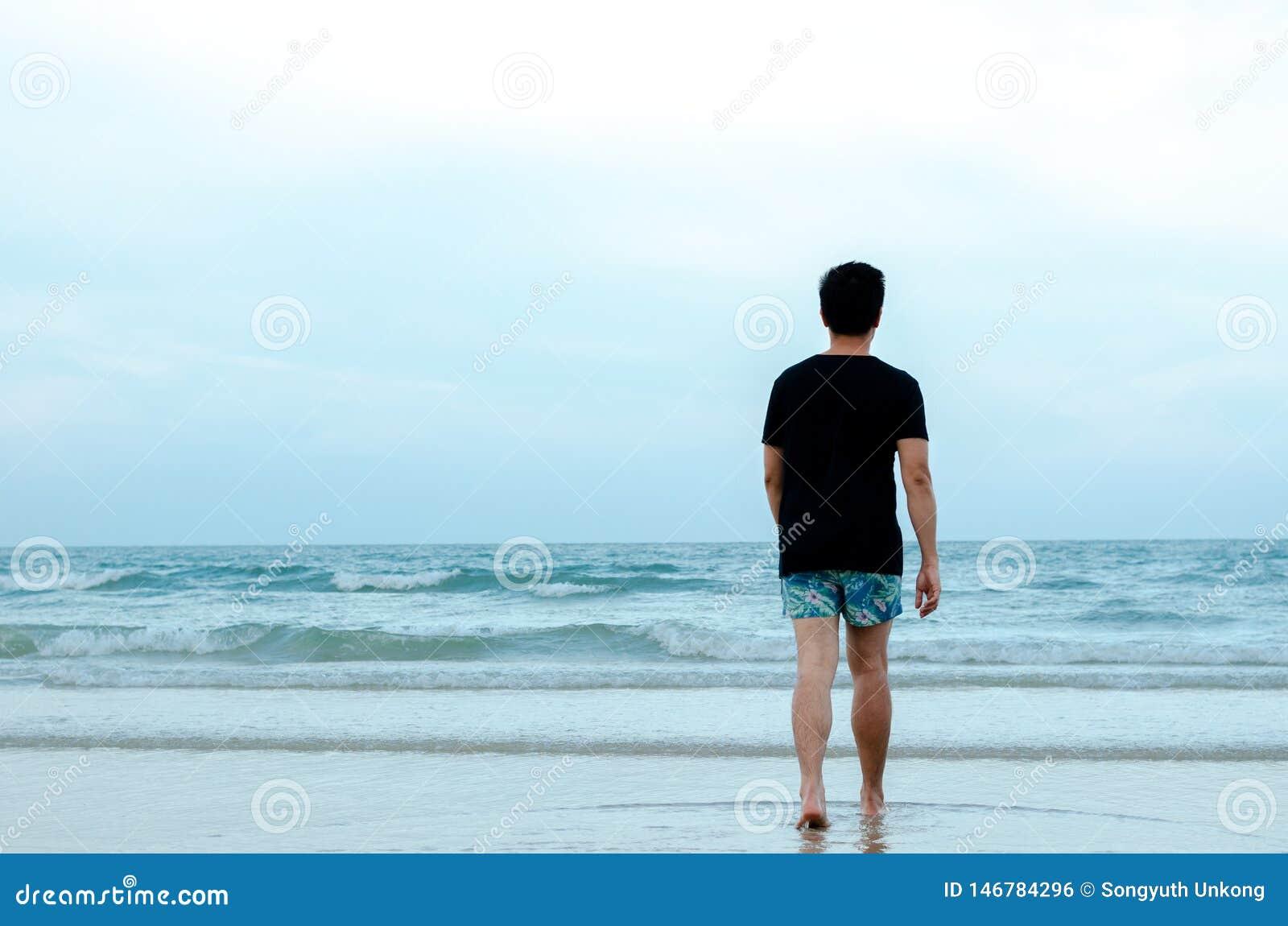 Osamotniony Azjatycki mężczyzna chodzi samotnie na plaży