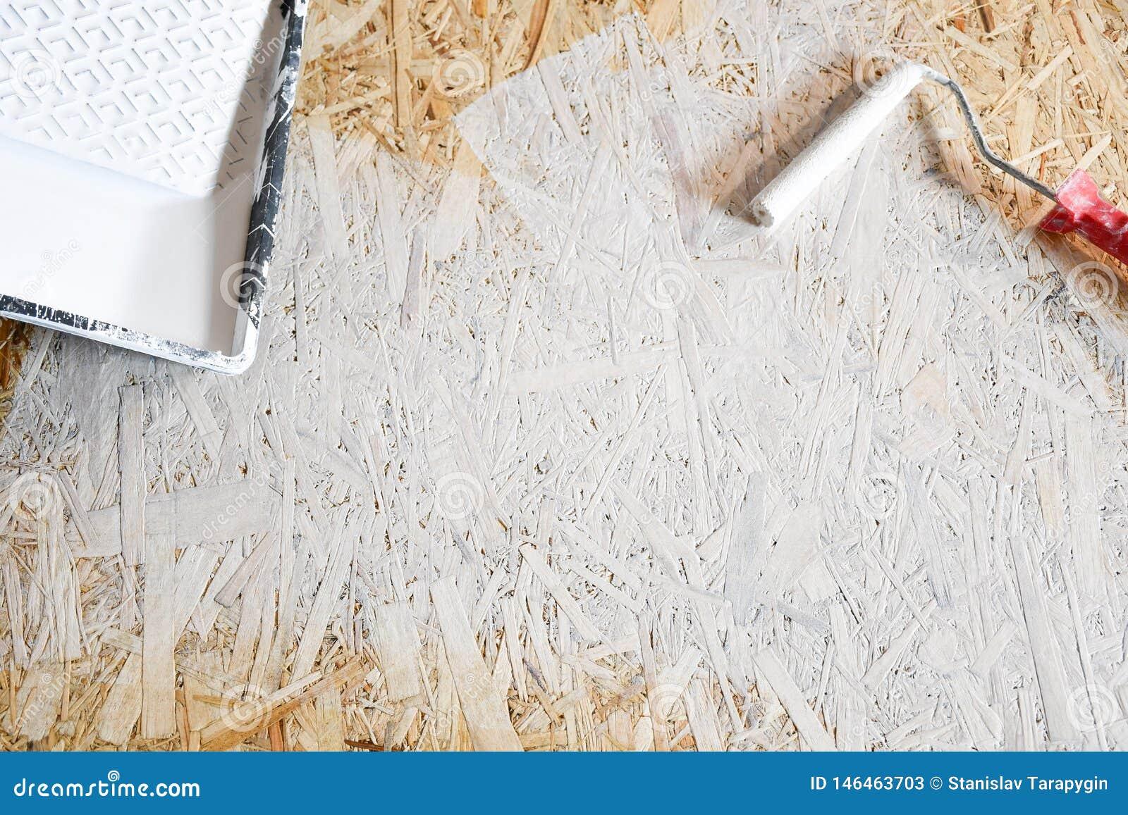 Osbplaat met witte verf met een rol wordt geschilderd die