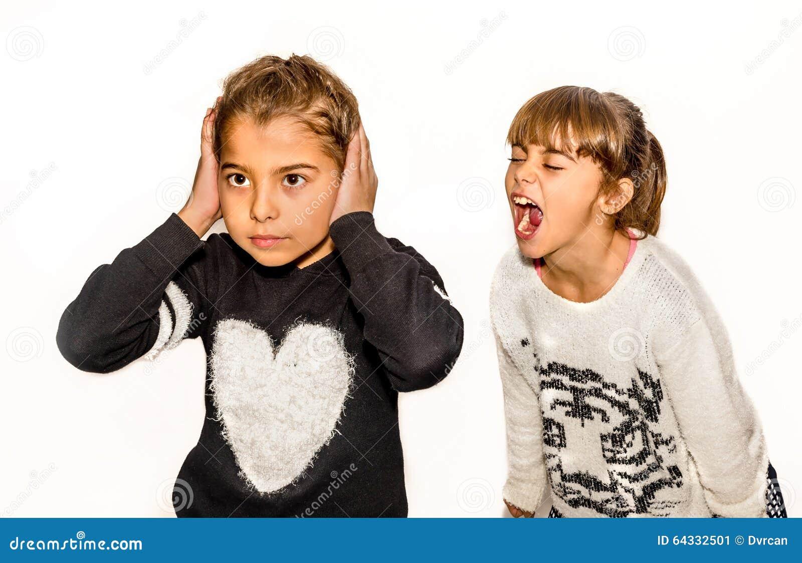 Osiem roczniaka dziewczyna jest gniewny i krzyczy przy jej siostrą Isol