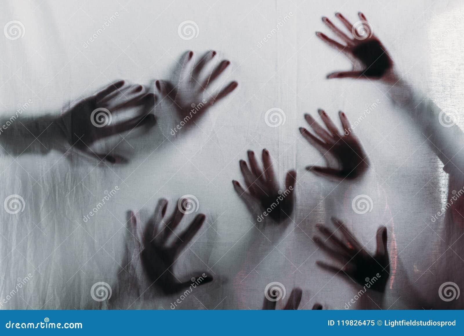Oskarpa läskiga konturer av mänskliga händer som trycker på frostat exponeringsglas