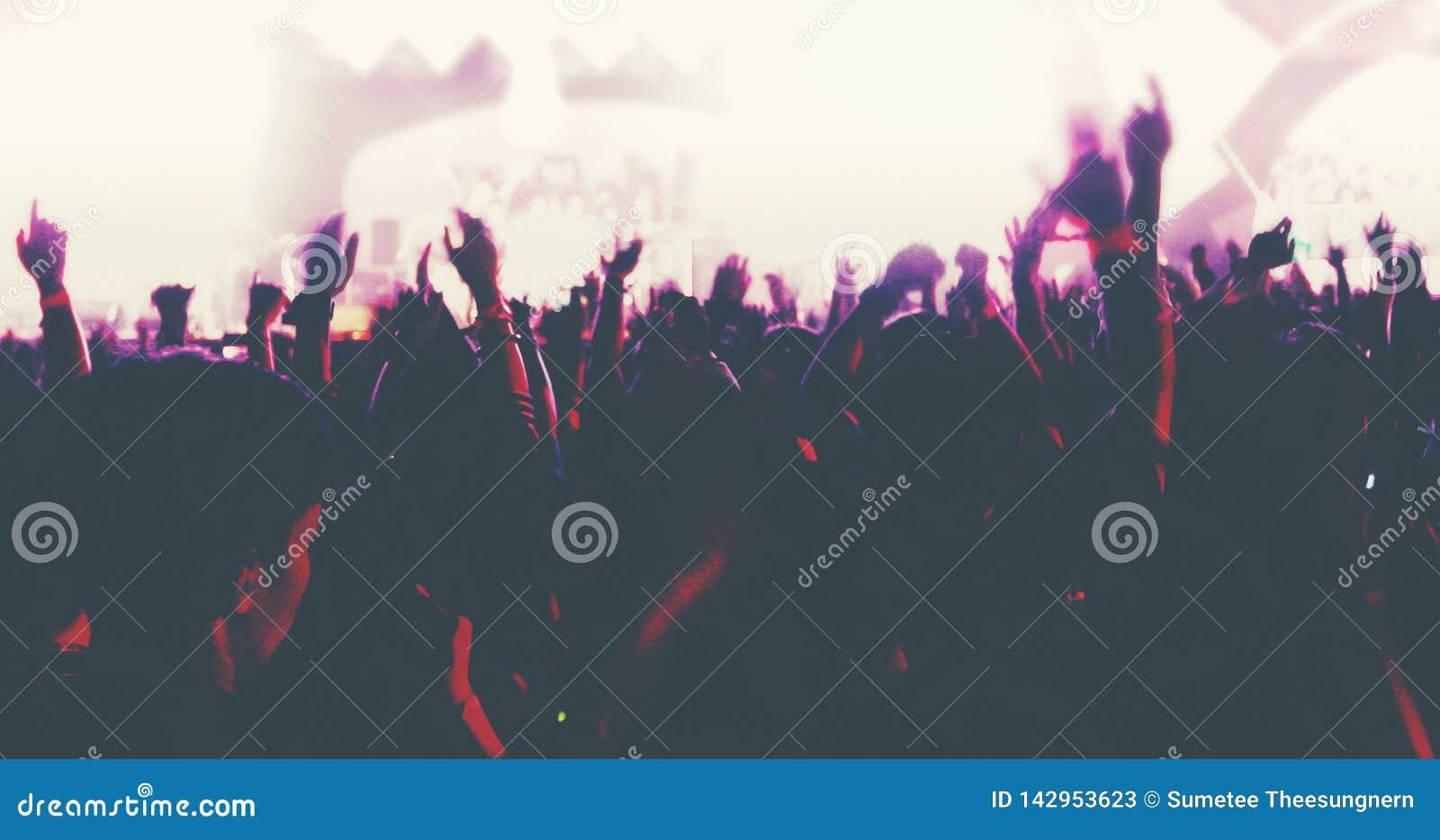 Oskarpt av konturer av konsertfolkmassan på den bakre sikten av festivalfolkmassan tänder att lyfta deras händer på ljus etapp